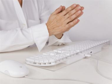 Hands in prayer over keyboard