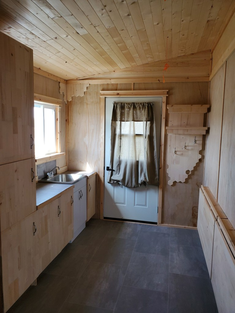 Interior of mobile studio showing the entry door and ample storage in the kitchen. The space is done in light wood with grey flooring.