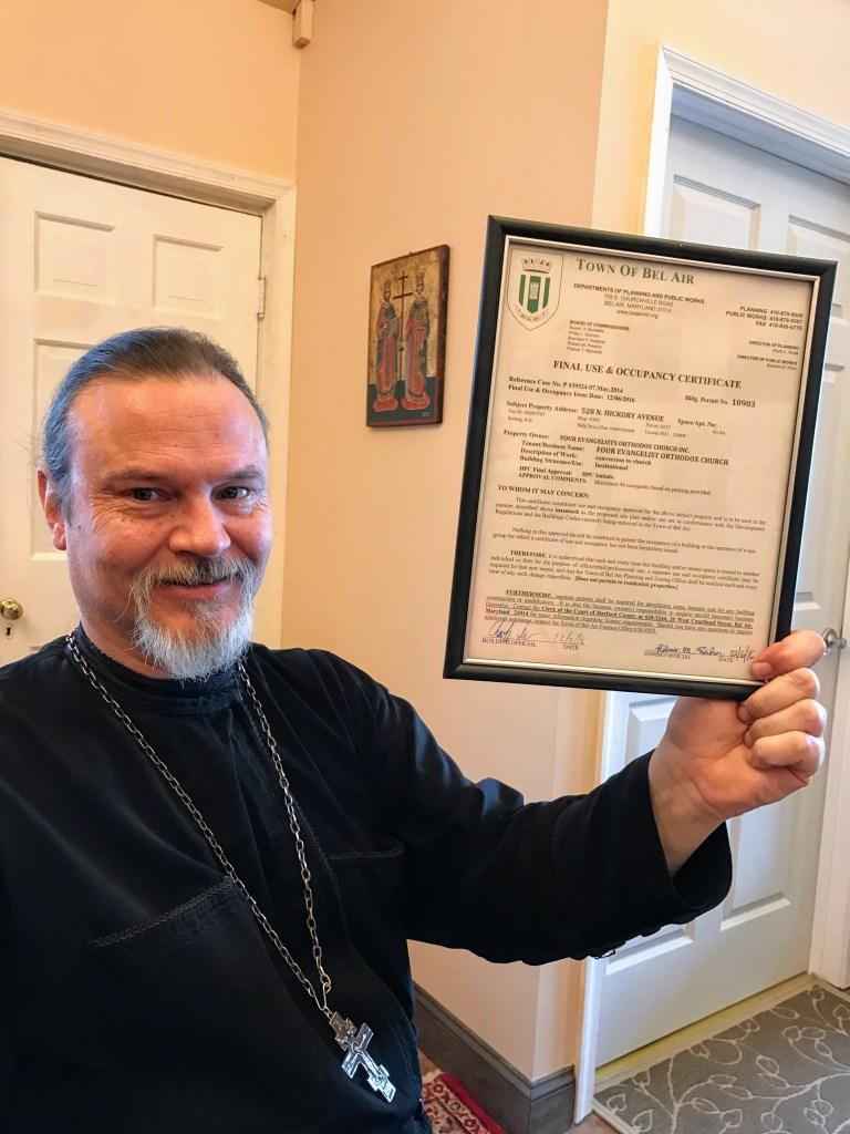 Fr. Gregory holding our long awaited occupancy permit