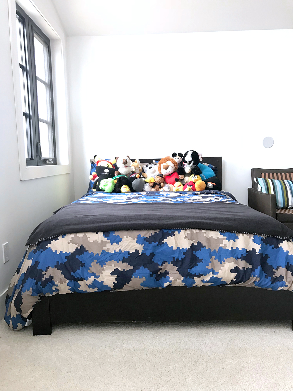 Boys bedroom before: a bed full of stuffed animals provides the only colour in the room