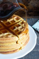 a fluffy stack of lightly spiced pumpkin flavored waffles on a white plate is shown with rich syrup being slowly poured on top and dripping down the edge