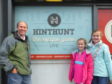 Family standing next to the HintHunt sign