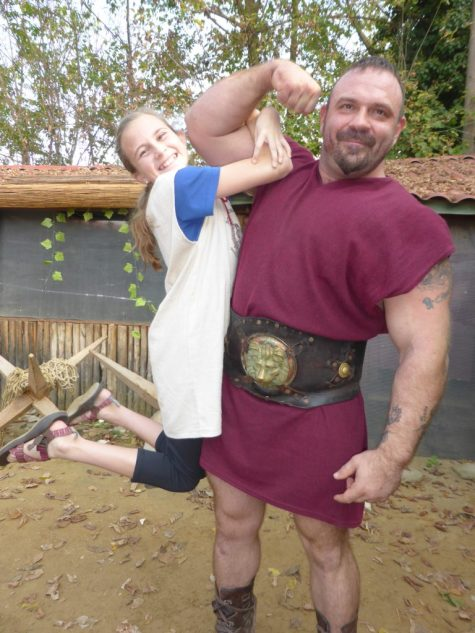 Girls hangs from gladiator's huge bicep