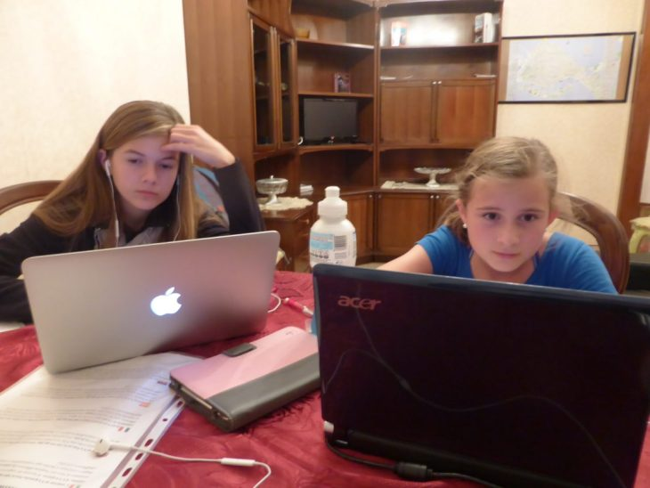 Image of two girls working on Acer and MacBook Air