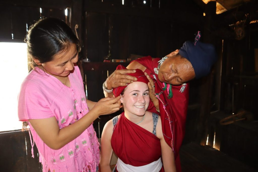Kayah women dress tourist in lacquer leg rings and traditional attire