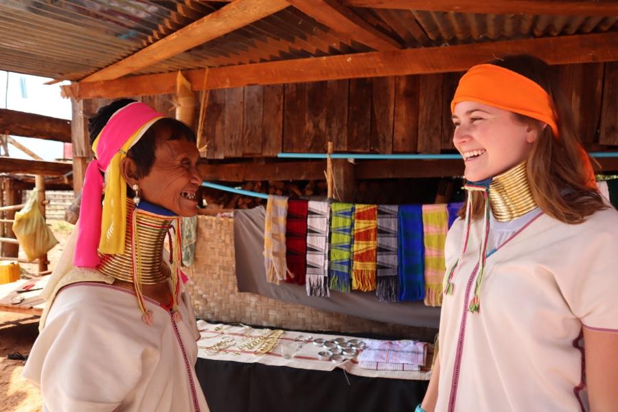 Long Neck Paduang woman laughs with tourist in Kayan village in Myanmar