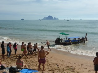 Locals and tourists work together to pull the stuck longtail out of the water
