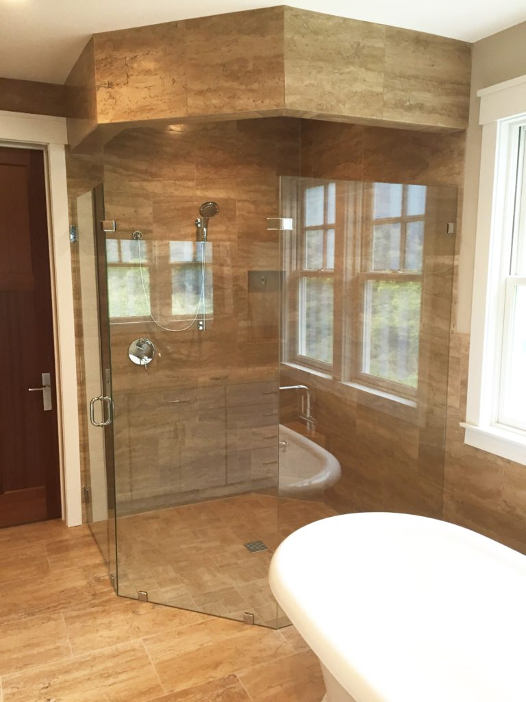 Full shower enclosure tiled with stone tile