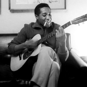 Sam Cooke smoking a cigarette and playing a guitar