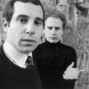 Paul Simon (in the foreground) and Art Garfunkel (in the background) in front of a wall covered in graffiti. Both men are wearing black sweaters. Simon is also wearing a shirt and tie. Garfunkel is holding a cigarette.