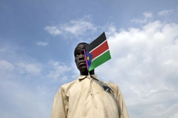 A Sudanese man holds the national flag attending a cultural festival to celebrate the South Sudan's anniversary July 7, 2012 in Juba, South Sudan. (Paula Bronstein/Getty Images)