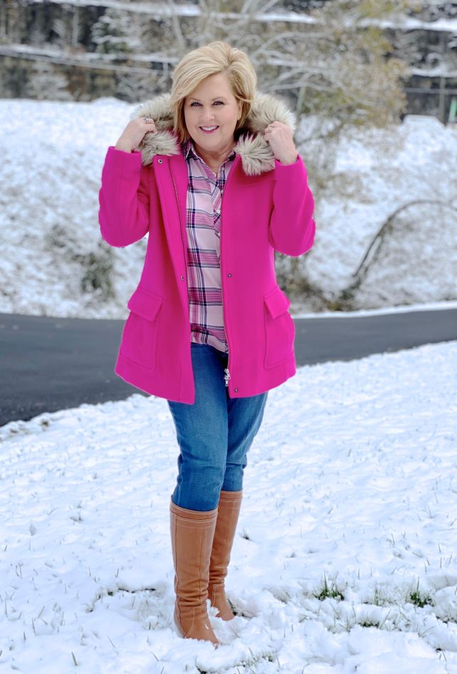 A blonde woman in the snow with a bright pink coat with a faux fur hood and boots