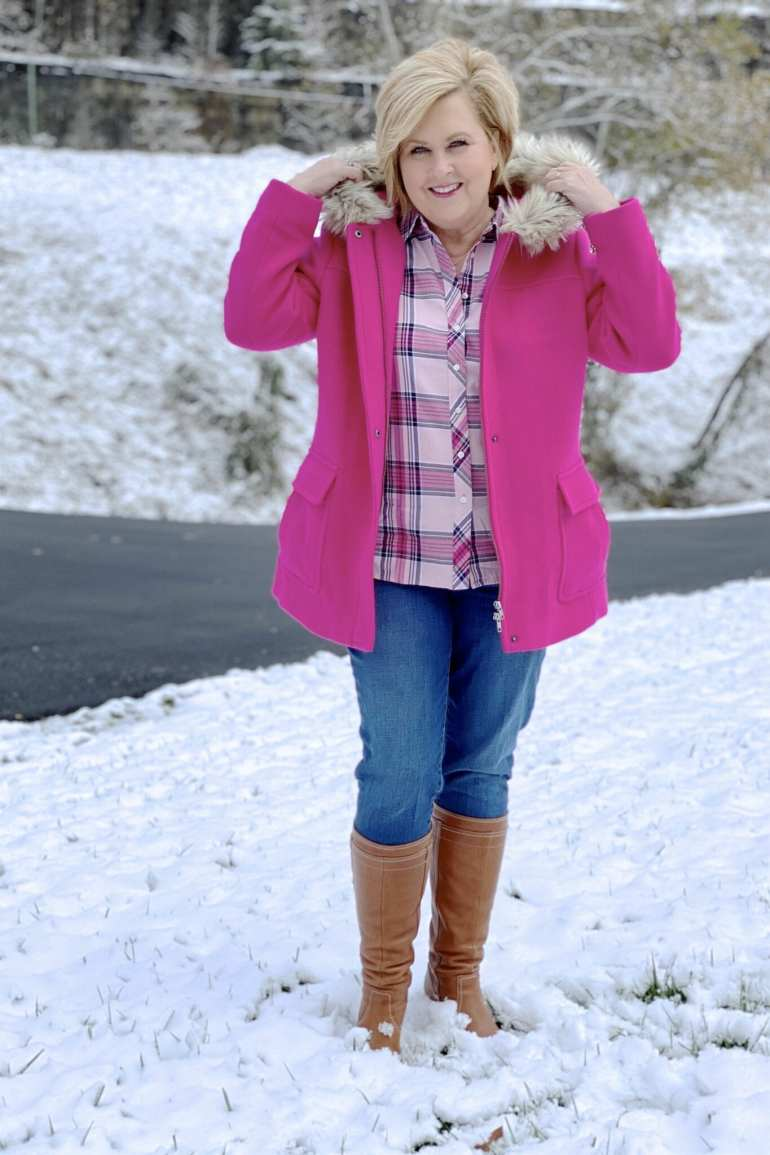 A blonde woman in snow with a bright pink coat with a faux fur hood
