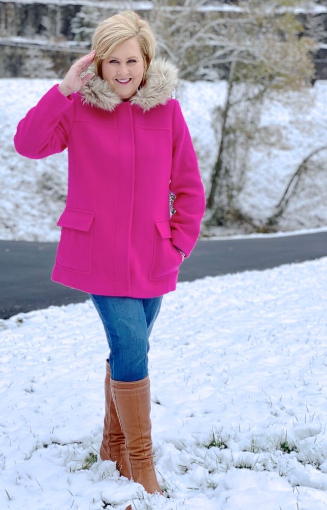 A blonde woman in the snow with a bright pink coat with a faux-fur hood