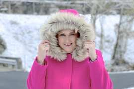 A blonde woman in the snow with a bright pink coat with a faux fur hood pulled up
