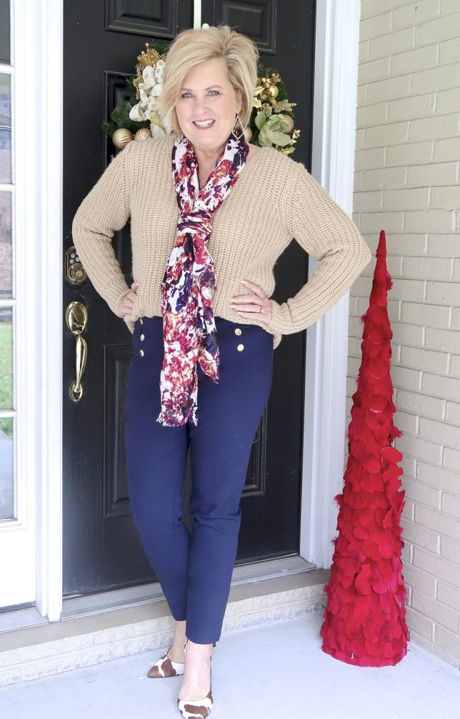 A gold sweater and navy pants worn with cow print pumps and a scarf by Fashion Blogger 50 Is Not Old