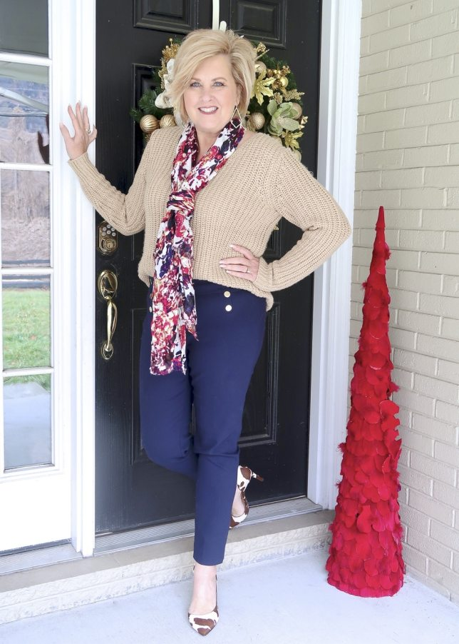 A gold sweater and navy pants worn by Fashion Blogger 50 Is Not Old