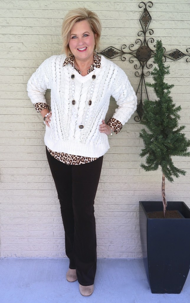 Fashion Blogger 50 Is Not Old wearing an ivory cable knit sweater with brown pants and a leopard print shirt