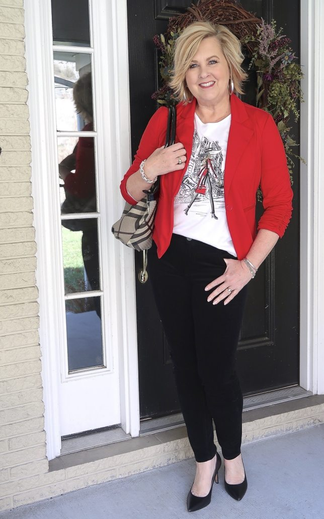 Fashion Blogger 50 Is Not Old looks stylish in black pants, and a graphic tee
