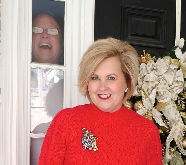 Fashion Blogger 50 is not old wearing a red sweater dress with man in background