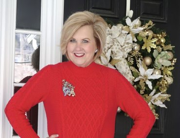 Fashion Blogger 50 is not old wearing a red sweater dress with Christmas pins