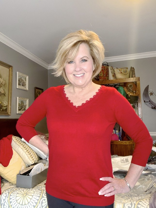 Fashion Blogger 50 Is Not Old holds a try on session with a red sweater