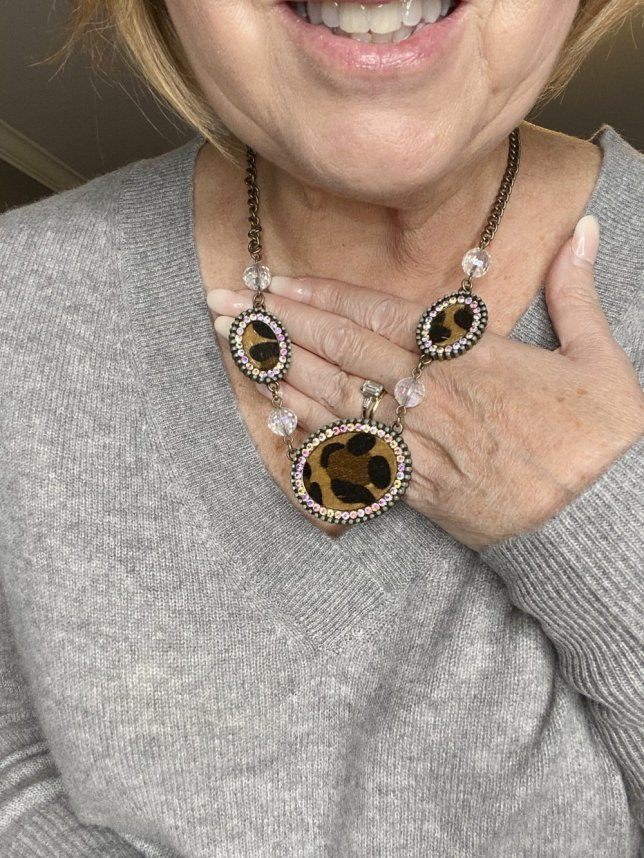 Fashion Blogger 50 Is Not Old holds a try on session shows an up close view of a leopard print necklace