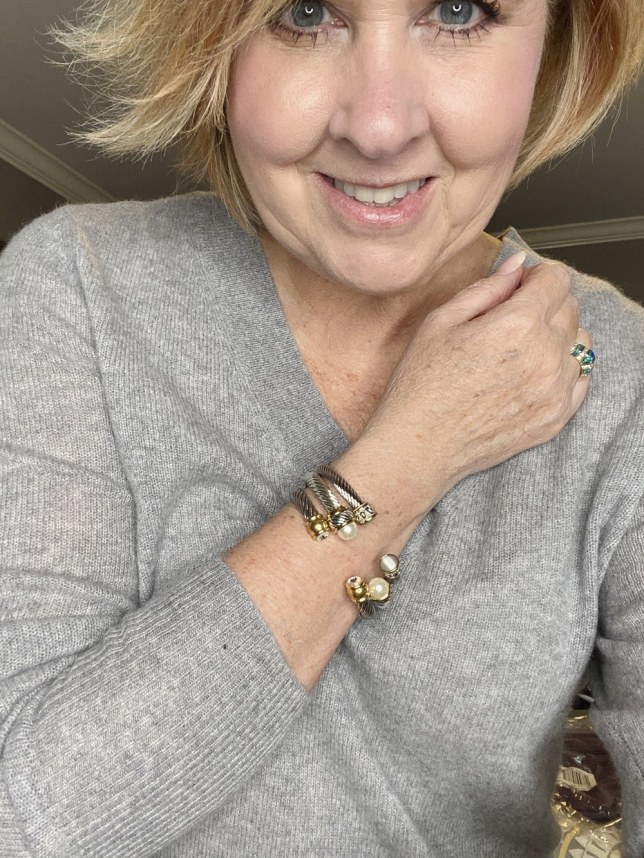 Fashion Blogger 50 Is Not Old holds a try on session and shows 3 silver bracelets