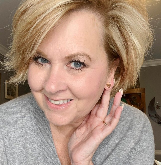 Fashion Blogger 50 Is Not Old holds a try on session and shows a tiny Tory Burch earring