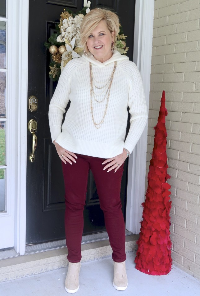 A relaxing outfit consisting of a hoodie sweater and maroon skinny pants by Fashion Blogger 50 Is Not Old