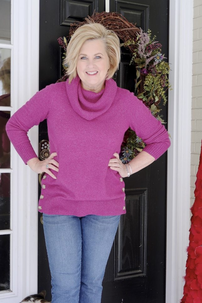Fashion Blogger 50 Is Not Old wearing a bright colored fuchsia sweater with buttons down each side