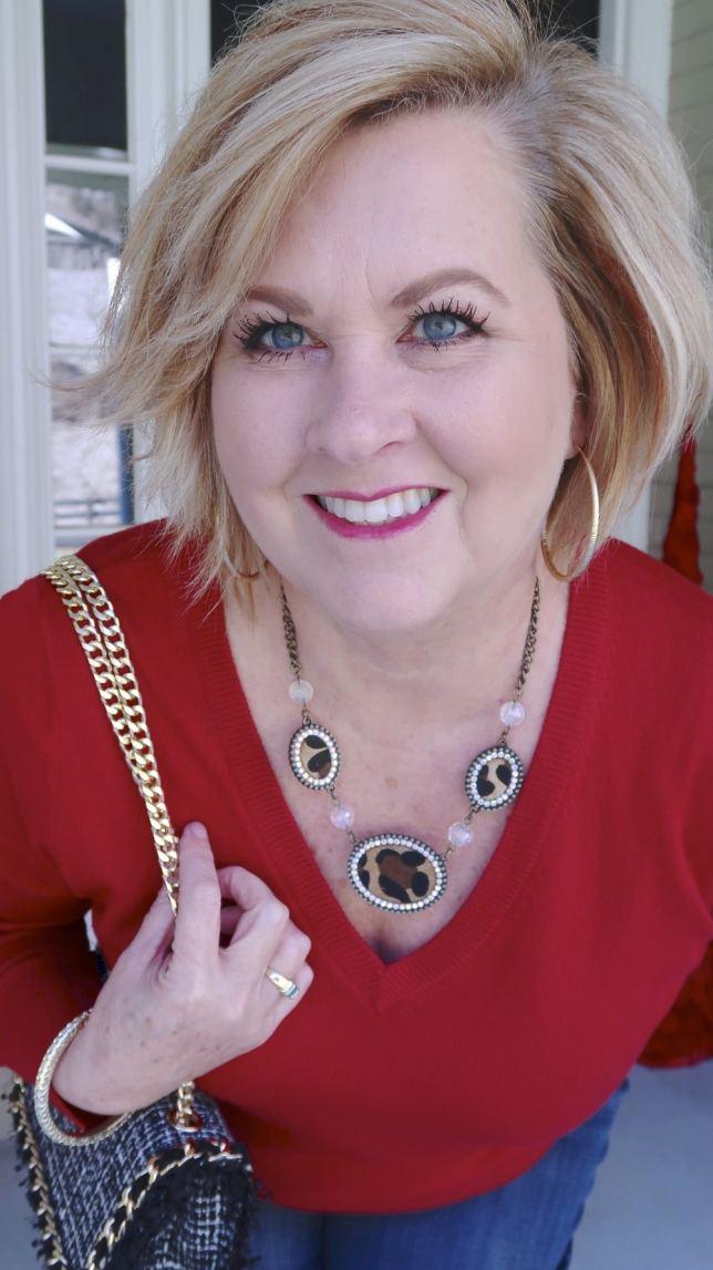 Fashion Blogger 50 Is Not Old is wearing a leopard print necklace with a red sweater