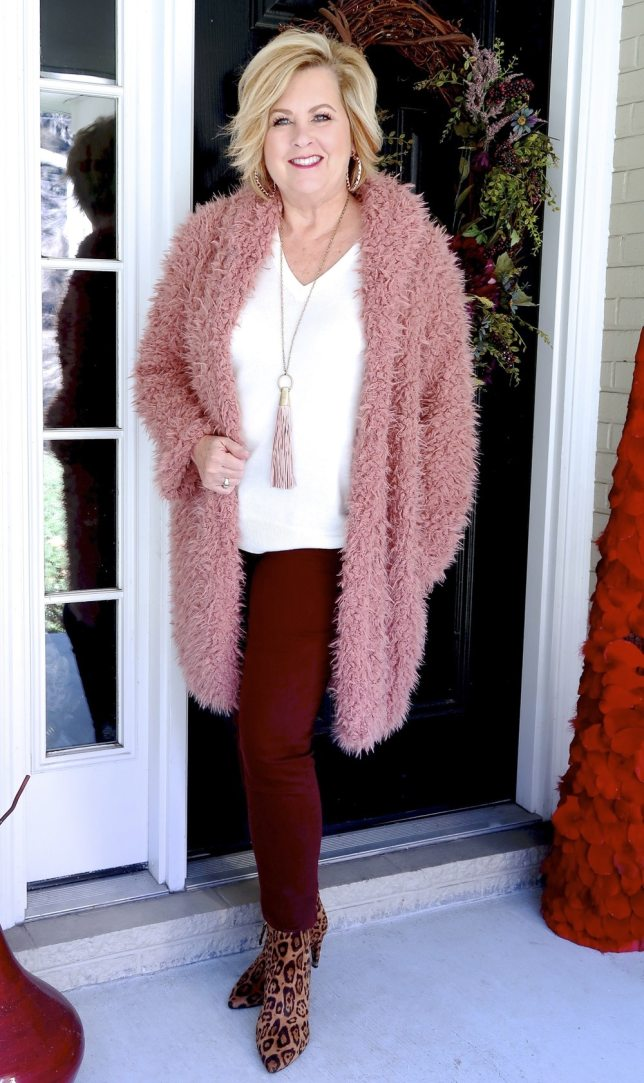 Fashion Blogger 50 Is Not Old is wearing a pink sherpa coat with burgundy pants and animal prints boots.
