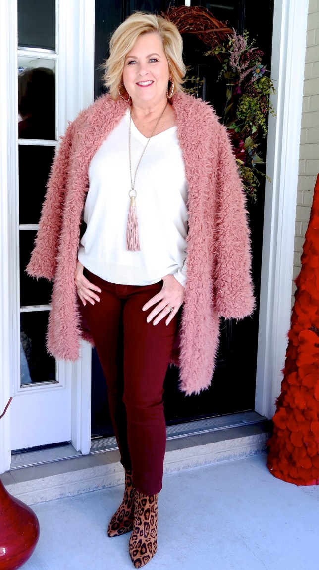 Fashion Blogger 50 Is Not Old is wearing a pink teddy bear coat with burgundy pants.