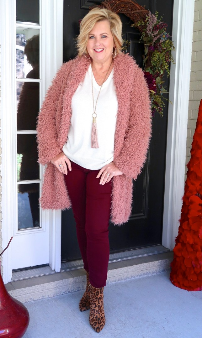 Fashion Blogger 50 Is Not Old is wearing a pink sherpa warm and cozy coat with burgundy pants.