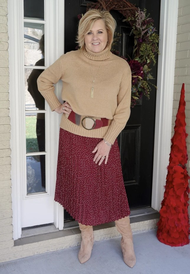 A classic turtleneck sweater belted with a burgundy skirt worn by fashion blogger 50 Is Not Old