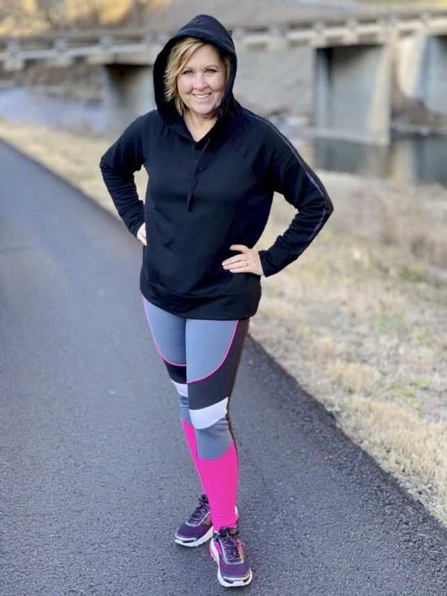 Fashion Blogger 50 Is Not Old wearing pink and gray Avia leggings and a black hoodie from Walmart
