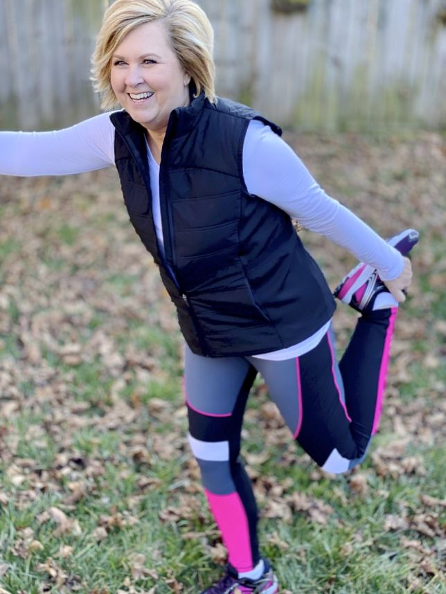 Fashion Blogger 50 Is Not Old wearing Avia leggings and a quilted vest from Walmart stretching her leg