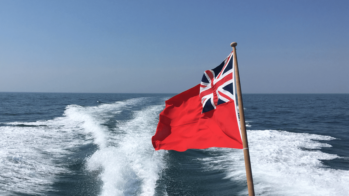 Red ensign and motorboat wake