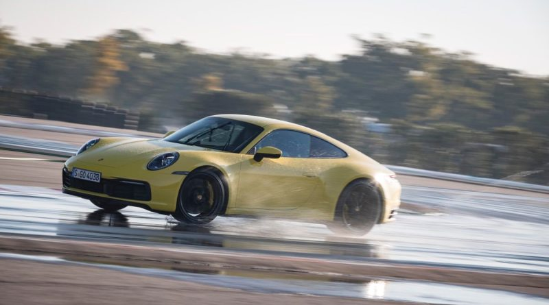 Yellow Porsche 911 cornering with the wetness detection system