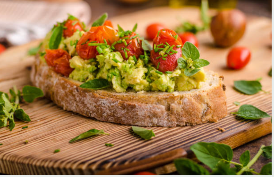 avocado toast with smashed avocado on one slice of bread sitting on a wooden chopping board, spinach leaves, chives and tomatoes top the toast with an avocado seed in the background.