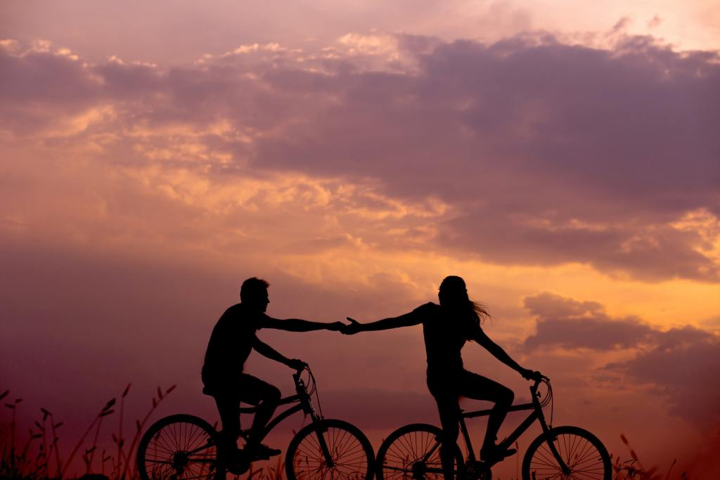 the silhouette of a man and woman riding two bikes while reaching out to touch each others hand. the sky is orange as if riding at dawn.