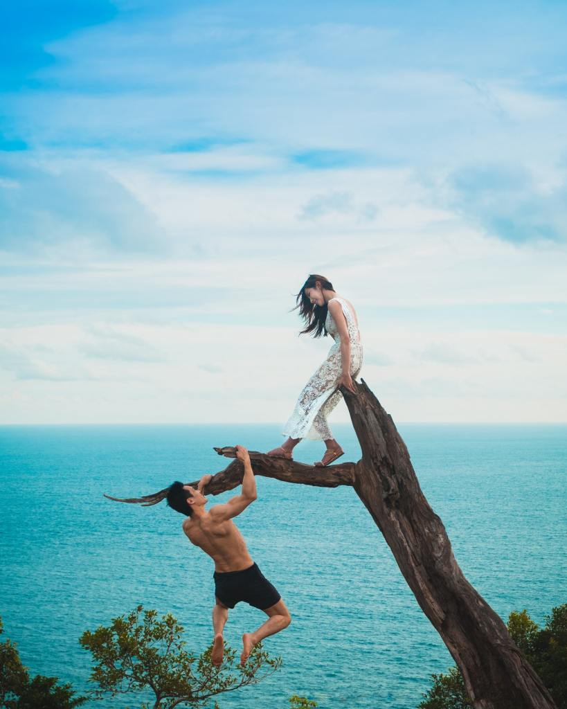 A woman sits on the top of a dead tree stump over water, while a man hangs from a limb trying to impress her the sky is bright and blue and the water is spectacular great blue.