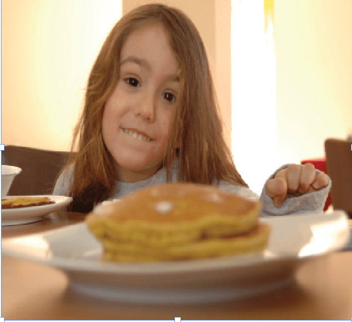 A young child smiles at a plate of pancakes made with Homemade pancake mix
