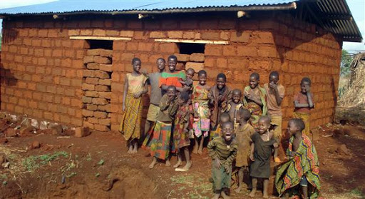 Burundi Africa shows a brick hut and a large family in poverty with he question how can they be happy.