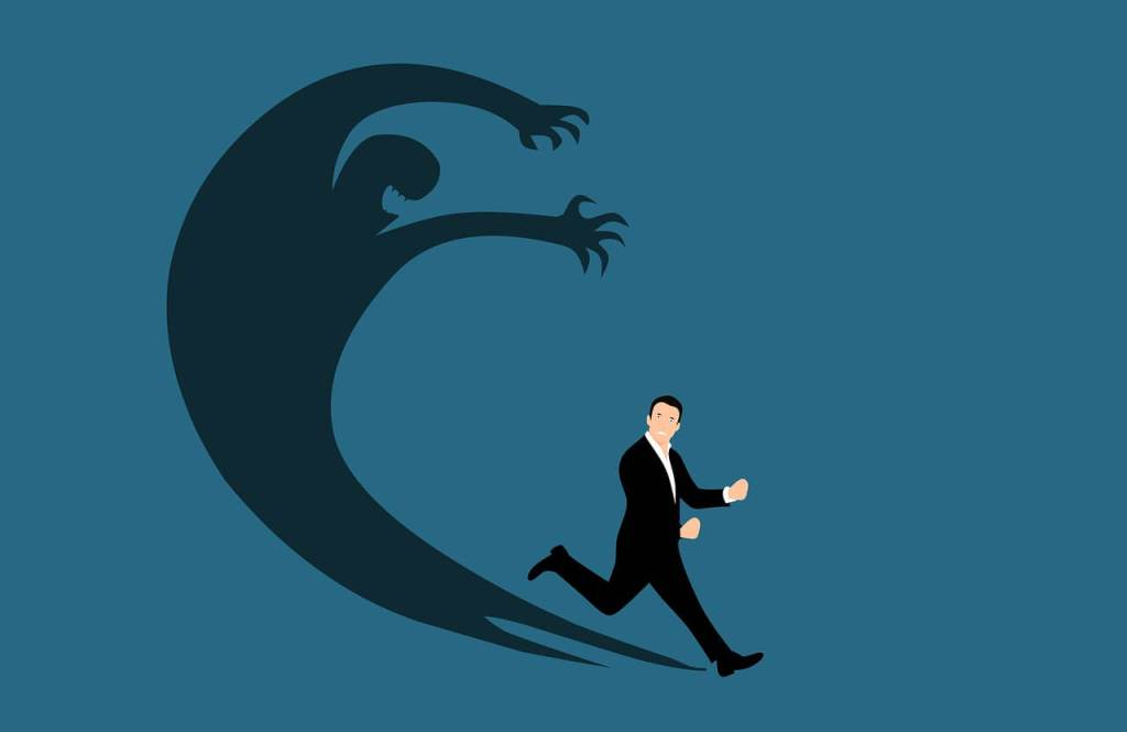 The fear of failure is depicted in a large shadow of evil over a man who's running from it.