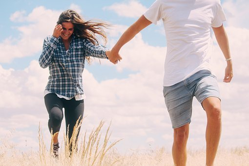 A man pulls a woman walking through dry grass to get exercise daily.