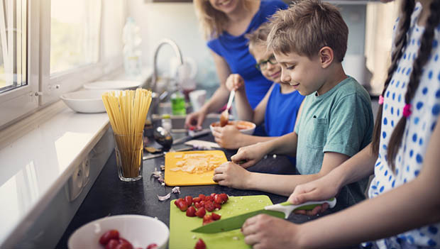 Kids learning to cut vegetables, each with a different chopping board.