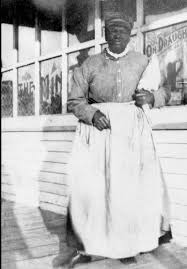 Stagecoach Mary in a white apron it looks like she's standing outside of her restaurant 1800's