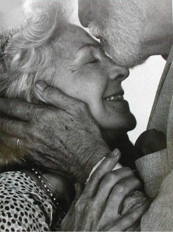 A senior could, the man is kissing her on the forehead and she has a loving smile on her face.